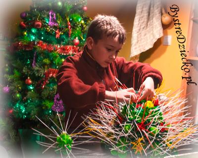 Choinka ekologiczna z surowców wtórnych, plastikowe nakrętki - upcycling w rękach dziecka